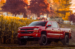 Photo of red pickup truck in front of corn stalks and fall leaves