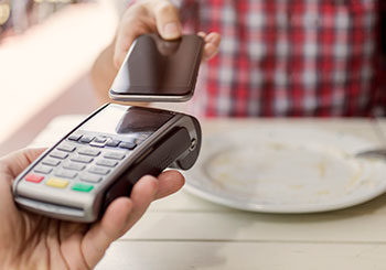 person using phone for contactless payment