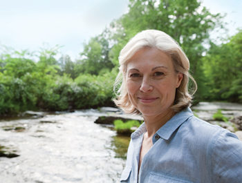smiling blonde woman in front of stream