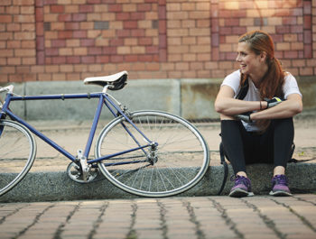 woman sitting on curb next to bicycle