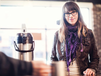dark haired woman in glasses at coffee shop