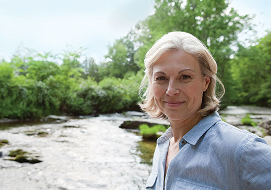 Mature woman standing in front of river