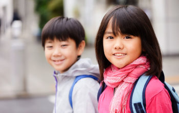 two smiling dark haired children