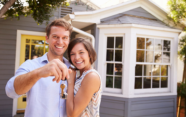 a man and woman in front of a house Eight-First-Time-Home-Buying-Mistakes