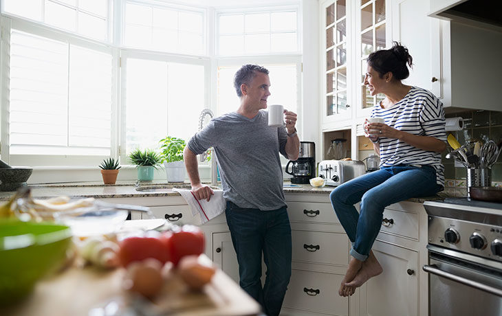 man and a woman talking in the kitchen
