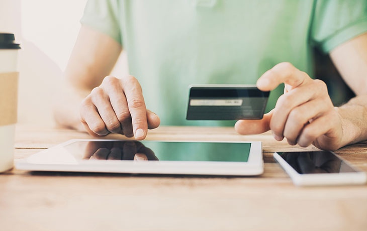man sitting at a tablet with a credit card
