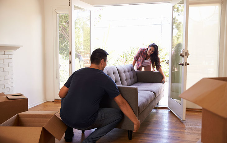 a man and woman moving a couch