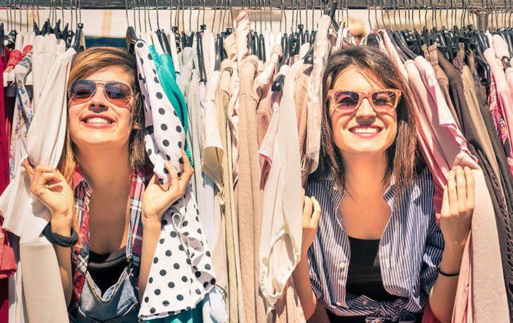 two smiling women amongst clothes
