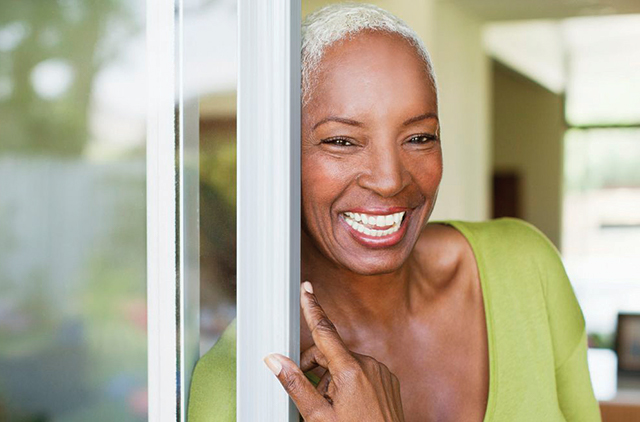 older female smiling at door