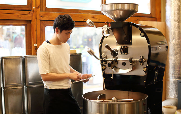 person with clip board near coffee roasting machine