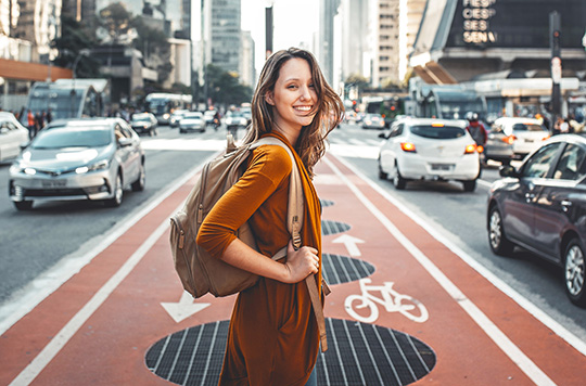 Young woman smiling as she walks down a South American city street because she's saving on travel expenses because she's paying no foreign transaction fees with her Sound credit card.