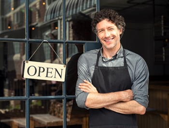 Cafe owner smiling standing outside