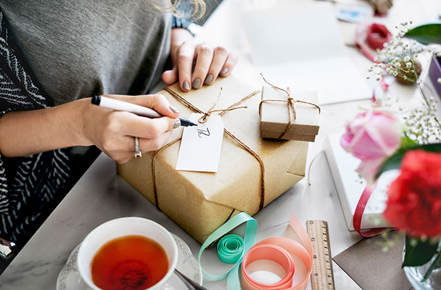 woman writing on the tag of a gift wrapped in brown craft paper in a square box tied with jute.