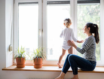 Mom and young toddler on window seat looking outside