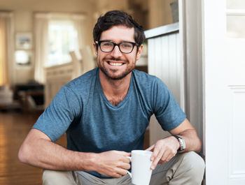 Smiling man holding a coffee cup at home