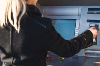 Young female using ATM