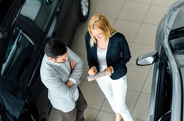 Man and woman talking over automobile paperwork