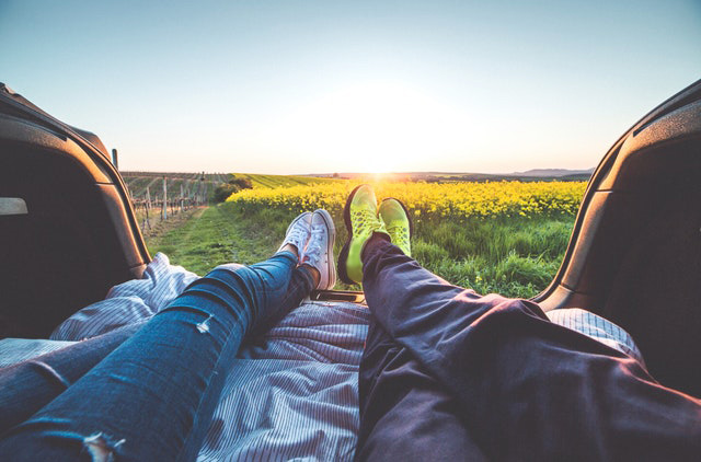 A couple laying in the back of a car watching the sunset over a field of yellow flowers