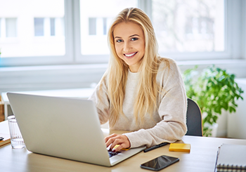 Professional woman working from home on laptop smiling at camera
