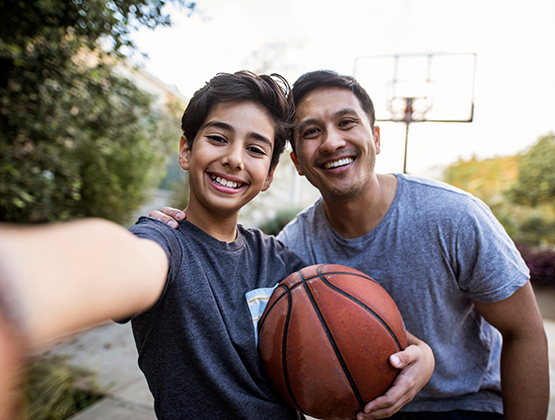 Father and son enjoying home basketball court
