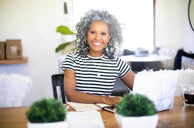 Woman professional at desk smiling at camera
