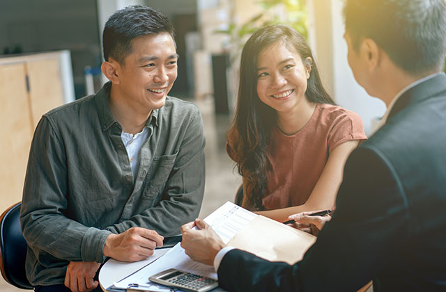 Young asian couple and agent disucss financial planning stock photo