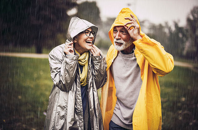 mature adult couple enjoying a walk in the rain