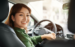 Woman smiling in drivers seat of car