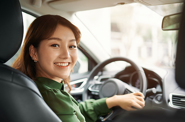 Woman smiling in drivers seat of car because she refinanced her car note and got a new auto loan from Sound Credit Union.