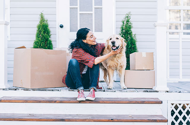 woman and dog sitting in front of house