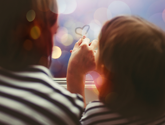 Little girl with her mother drawing heart on misted window glass