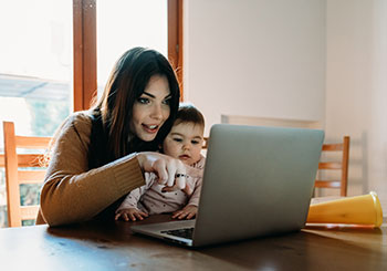 mother is working at home using computer while she's taking care of her daughte