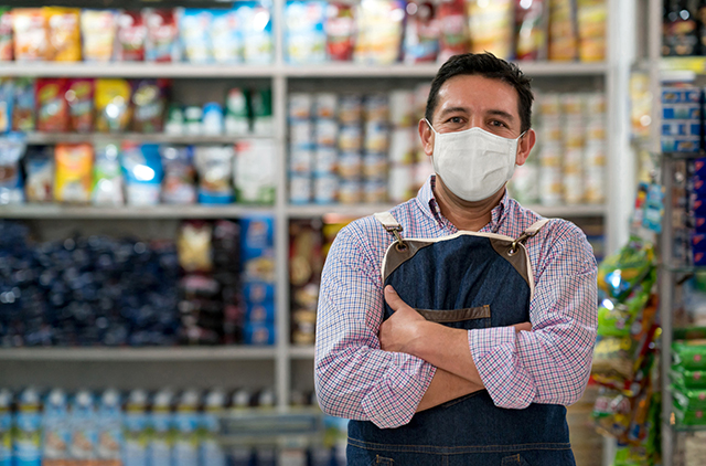 Small business owner in shop wearing a mask