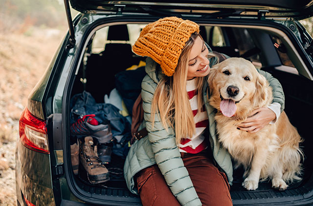 Hiker hugging their dog in the tailgate of a SUV