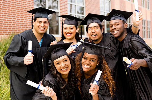 friends excitedly hold diplomas after college graduation
