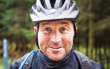 Muddy mountain biker smiling at camera with helmet on