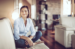 Woman sitting cross-legged on couch smiling at camera