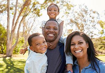 Family smiling at camera enjoying outdoors