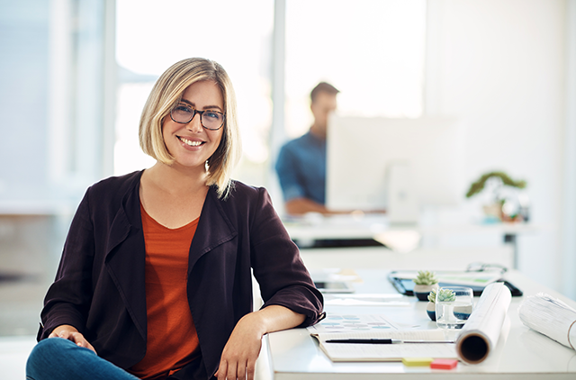 Happy professional with glasses smiling at camera from desk