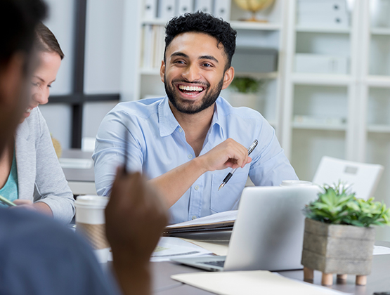 Businessman laughs while meeting with colleagues