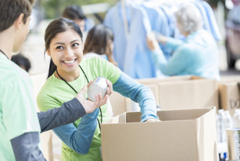 Male and female teenage food bank volunteers sort canned food items in cardboard boxes.