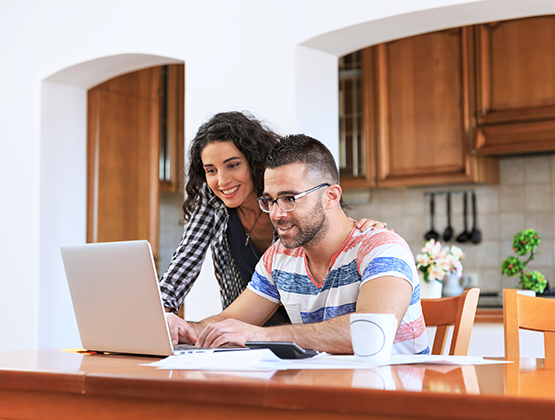 Couple working together on laptop in kitchen