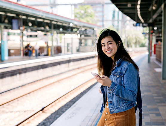 Student traveler on the go at a train station doing mobile banking with their smart phone