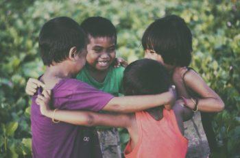 kids lauging and hugging in circle