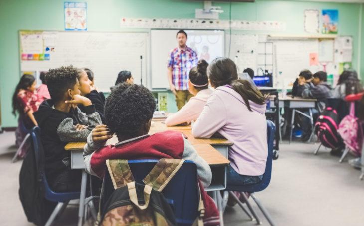 children in a classroom listening to the teacher