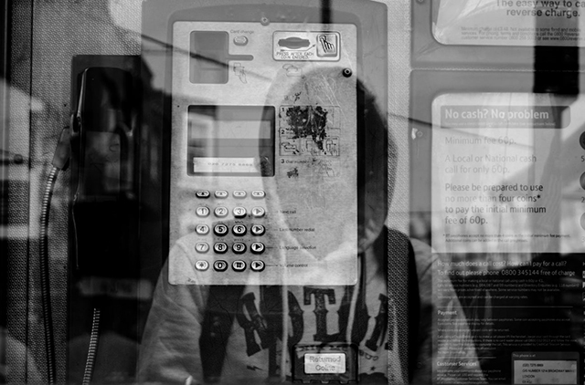 relfection of person in glass and payphone