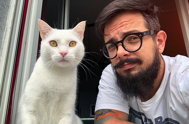 Bearded man with glasses looking out a window with a cat, pondering how to secure his information online.